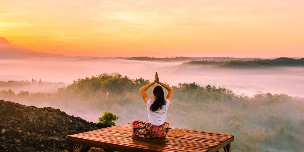 Young white lady doing yoga alone in the forest at sundown, sports played sitting down, sitting down sports, doing sports while sitting, what sports can i do sitting, lazy sports, weird sports, unusual sports, yoga, online sportsbooks, gamingzion